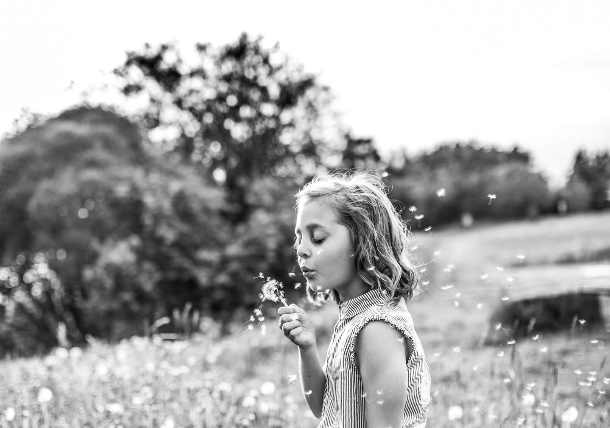 Perhekuvaus miljöössä tyttö puhaltaa voikukan haituvia Kouvola