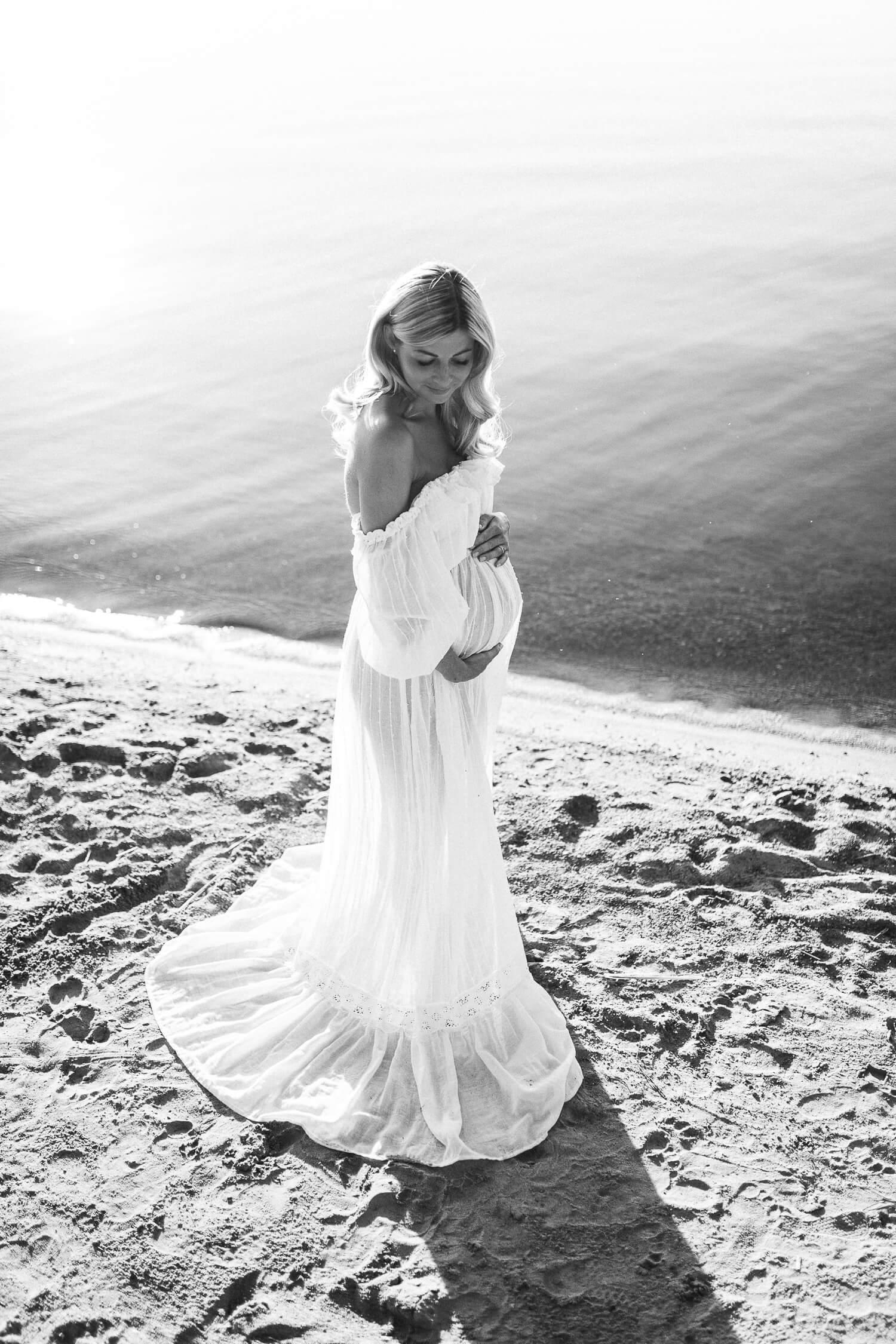 Kaunis odottava äiti rannalla